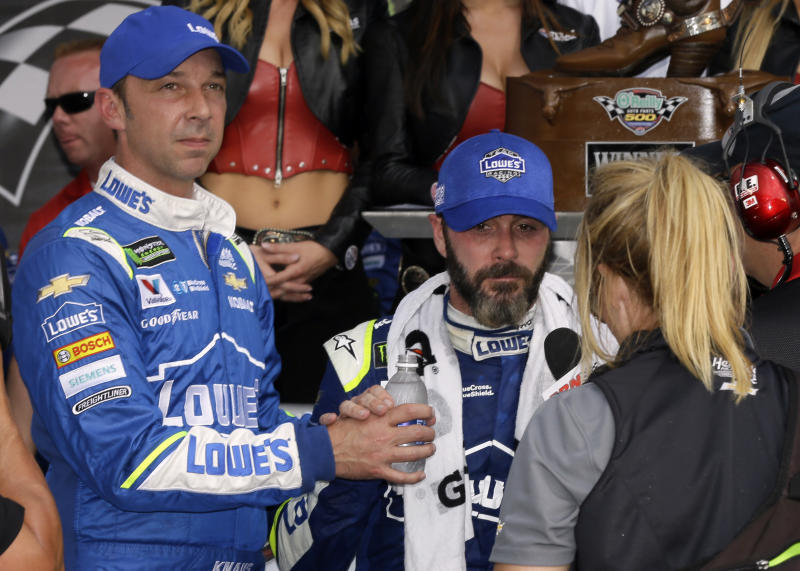"""Crew Chief Chad Knaus offers Jimmie Johnson a bottle of water as Johnson gives on broadcast interview in victory lane following his win in the NASCAR Cup Series auto race at Texas Motor Speedway in Fort Worth, Texas, Sunday, April 9, 2017. """"I'm not feeling the best, but we got into Victory Lane,"""" Johnson said before going to the infield care center to get treatment for apparent dehydration after his 81st career victory. (AP Photo/Tony Gutierrez)"""