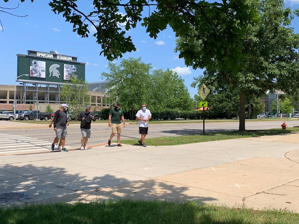 New Michigan State football defensive coordinator Scottie Hazelton, middle, prepares to cover his face with a bandana as he arrives with a group to go through COVID-19 testing Monday in East Lansing.