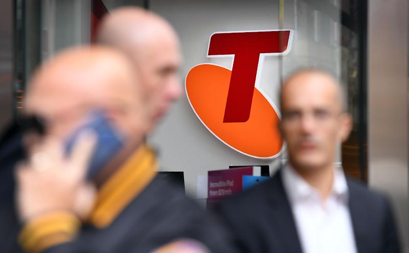 "People walk past a sign of telecommunications company Telstra in Melbourne on August 16, 2018. - Australia's dominant telecommunications company Telstra on August 16 warned of ""enormous challenges"" ahead as it posted an 8.9 percent slump in annual profit. (Photo by William WEST / AFP) (Photo credit should read WILLIAM WEST/AFP via Getty Images)"