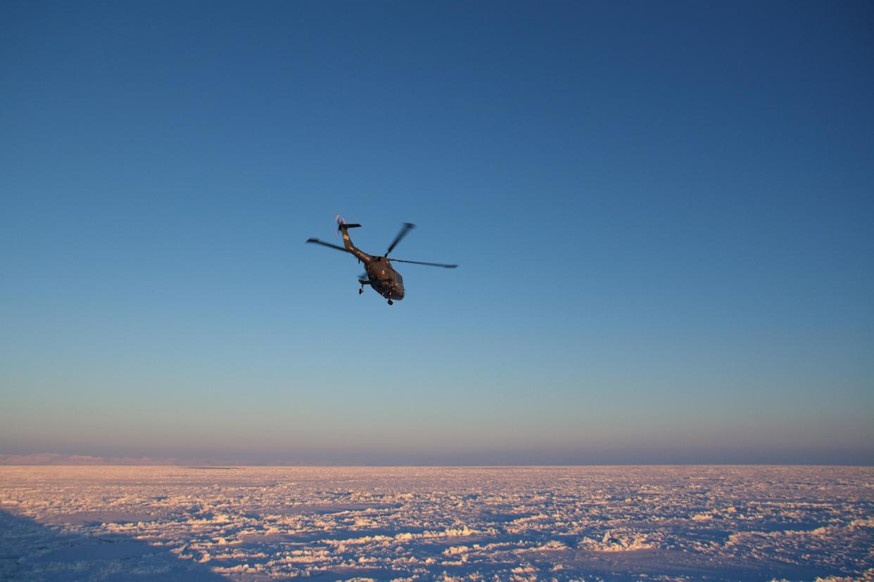 A helicopter takes off from a coast guard icebreaker, headed for Longyear city on Spitsbergen, Svalbard. The shadow of the ship can be seen in the lower left corner.