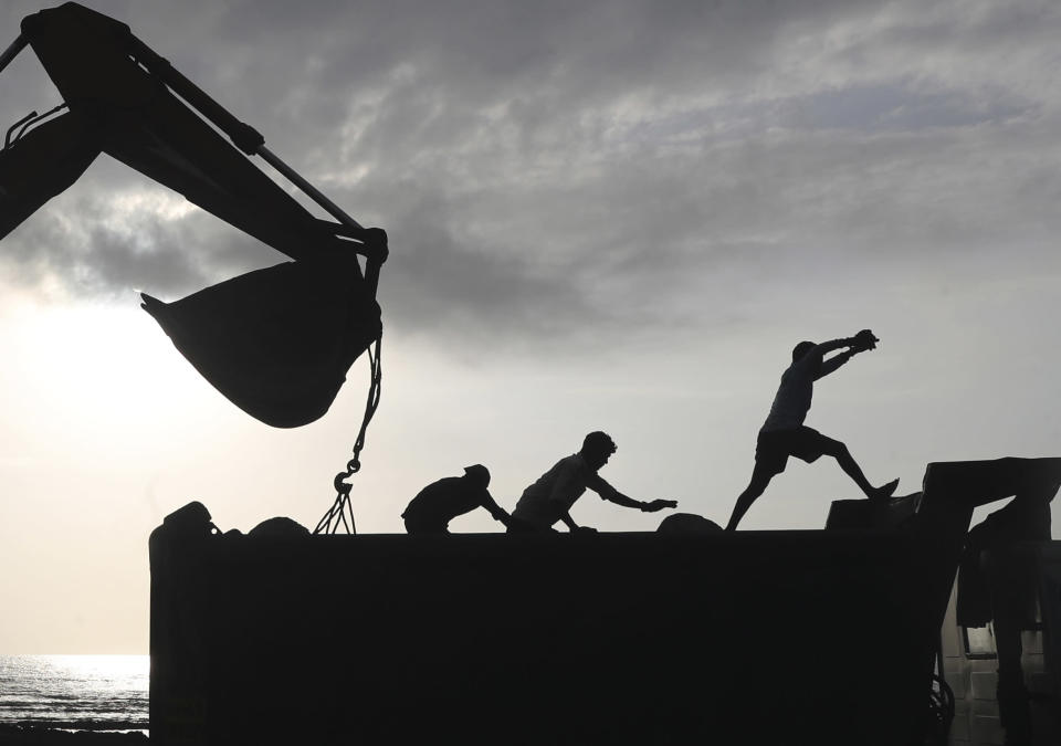 Workers use machinery at a coastal road project construction site in Mumbai, India, Thursday, Aug. 26, 2021. (AP Photo/Rafiq Maqbool)
