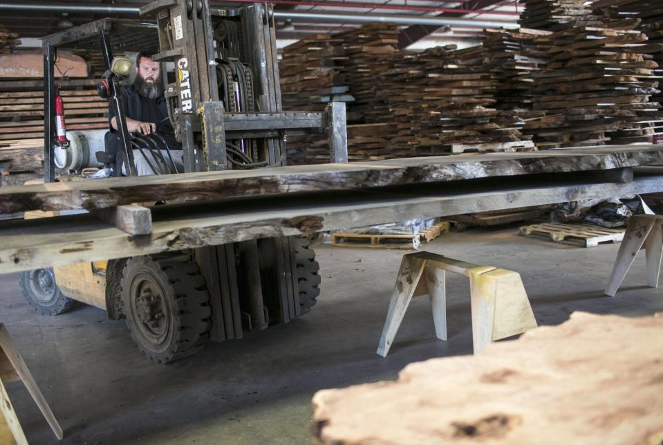 Landon Buck, owner of Redwood Burl Inc., works at the warehouse in Arcata, California June 13, 2014. Most of the shop's wood was cut more than 50 years ago and bought from private landowners. Picture taken June 13, 2014. REUTERS/Nick Adams (UNITED STATES - Tags: BUSINESS)