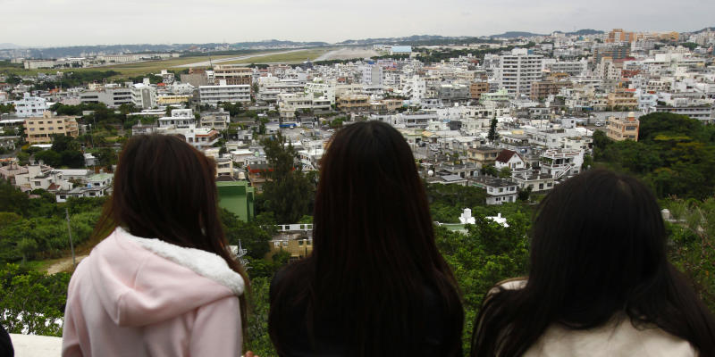 FILE - In this Dec. 17, 2009 file photo, high school students at an observation platform look at Marines Corps Air Station Futenma stretching beyond the residential area in Ginowan in Okinawa, southern Japan. About 9,000 U.S. Marines stationed on the Japanese island of Okinawa will be moved to the U.S. territory of Guam and other locations in the Asia-Pacific, including Hawaii, under a U.S.-Japan agreement announced Thursday, April 26, 2012. (AP Photo/Shizuo Kambayashi, File)