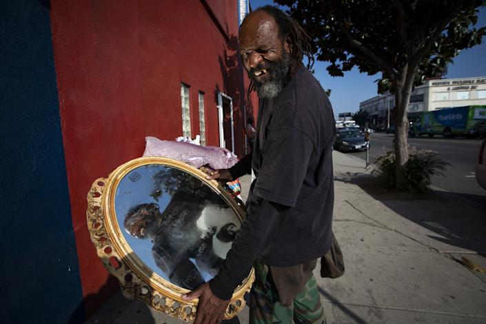 A man stands on a sidewalk holding an ornate mirror in both hands.