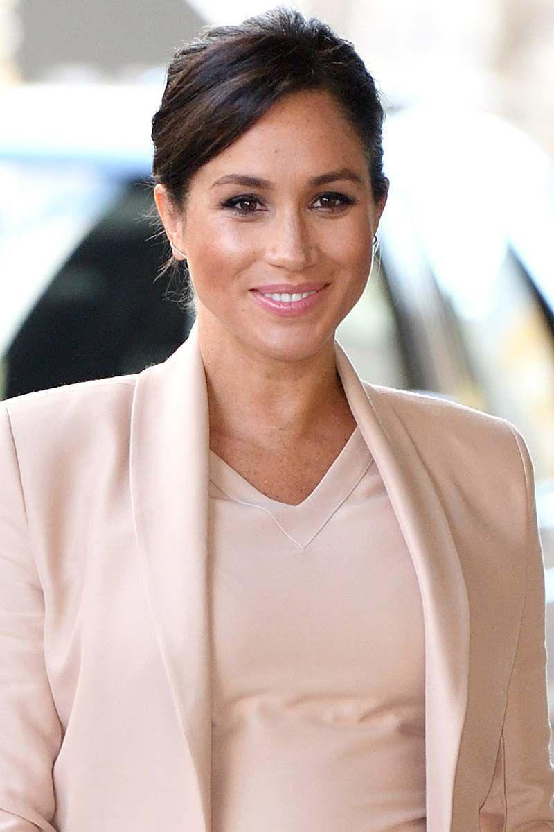 <p>The Duchess of Sussex topped off her monochrome look with a side part and simple updo.</p>