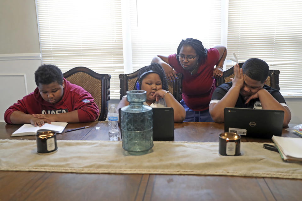Brittany Preston helps her daughter Brittani Preston, middle, with her class activities, as her 14-year-old son Joshua, left, and 15-year-old son Willie Preston study, Wednesday, Feb. 10, 2021, in Chicago. Brittany used to help her husband, Willie, with his small construction firm but with the coronavirus, she and her kids are mostly staying home. (AP Photo/Shafkat Anowar)