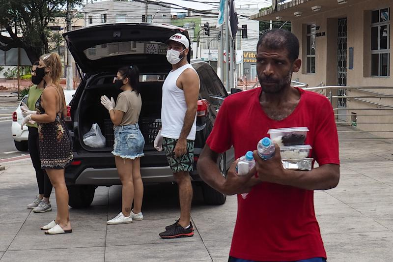 Volunteers distribute water and food to homeless people in Vitoria City, Brazil on April 5, 2020 during the coronavirus (COVID-19) pandemic. (Photo by Gilson Borba/NurPhoto via Getty Images)