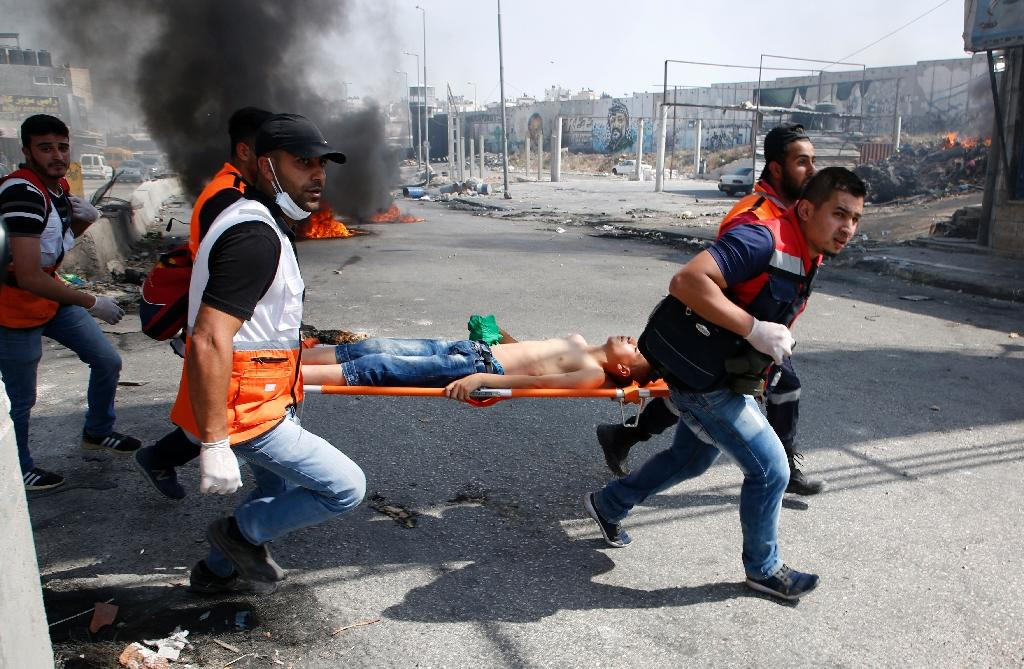 Palestinian medics evacuate a wounded protester during clashes with Israeli troops following a protest by Palestinians in support of prisoners on hunger strike, on May 22, 2017 at the Qalandia checkpoint in the occupied West Bank (AFP Photo/ABBAS MOMANI)