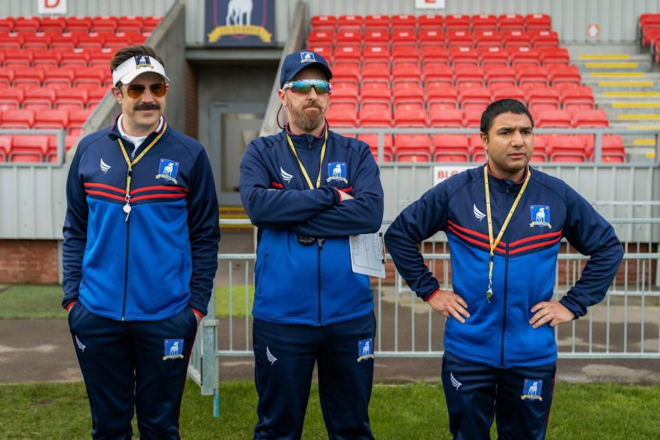 <ul> <li><strong>What to wear for Ted:</strong> A navy sweatsuit, a yellow whistle lanyard, a visor, aviator sunglasses, and his classic mustache. </li> <li><strong>What to wear for Coach Beard:</strong> Like Ted, Coach Beard sports a navy sweatsuit and a yellow whistle lanyard, but you can also grab a hat, sports sunglasses, and a clipboard. If you can grow a beard, that's just a bonus! </li> <li><strong>What to wear for Nate:</strong> Nate is the easiest of the three - just go with the sweatsuit and whistle, then channel Nate's sweet demeanor and newfound self-confidence.</li> </ul>