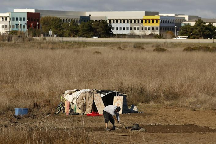 A person next to a makeshift shelter in a field with a building in the background