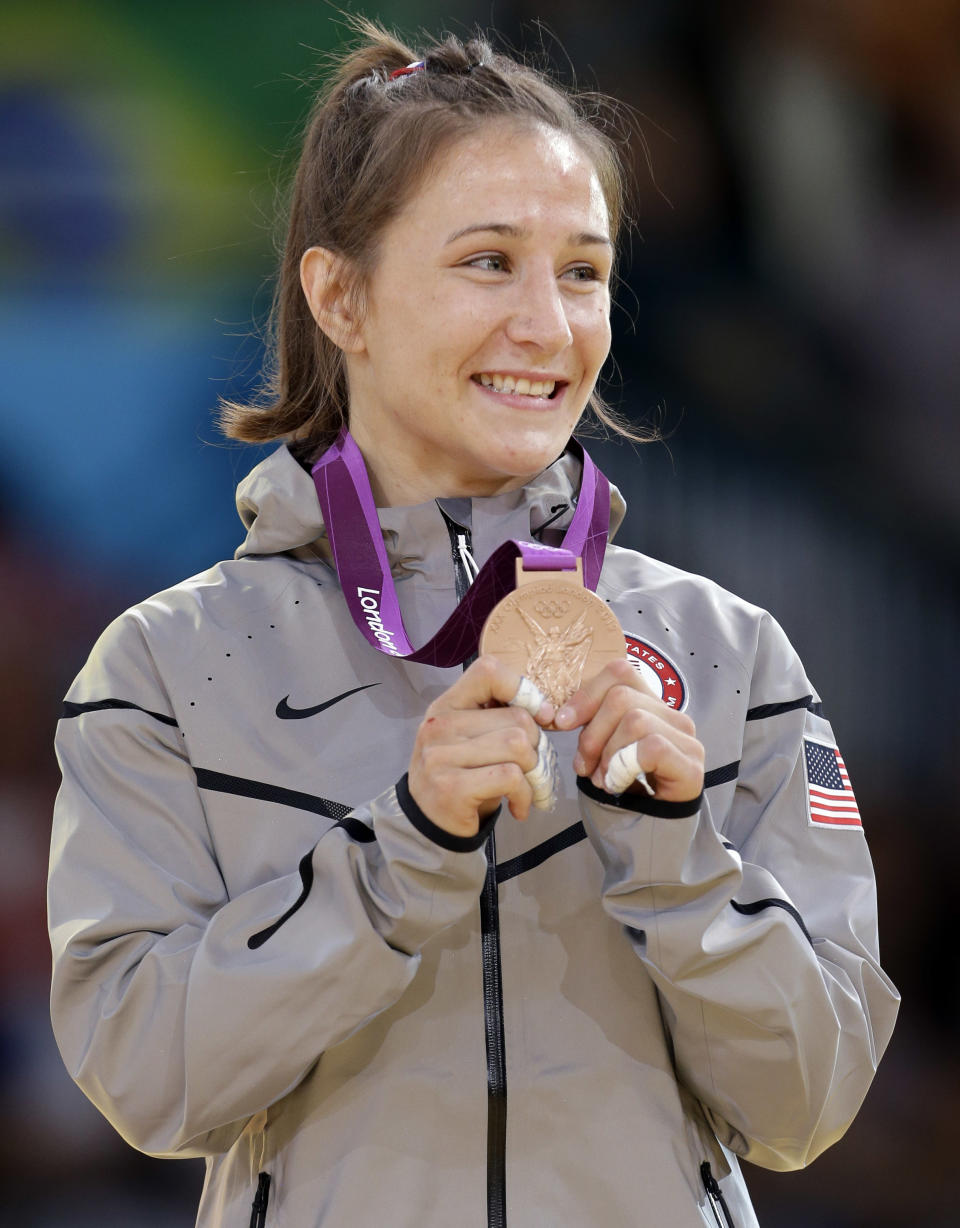 """Bronze medalist <a href=""""http://sports.yahoo.com/olympics/judo/marti-malloy-1134435/"""" data-ylk=""""slk:Marti Malloy"""" class=""""link rapid-noclick-resp"""">Marti Malloy</a> of the United States shows her award during the medal ceremony after the women's 57-kg judo competition at the 2012 Summer Olympics, Monday, July 30, 2012, in London. (AP Photo/Paul Sancya)"""
