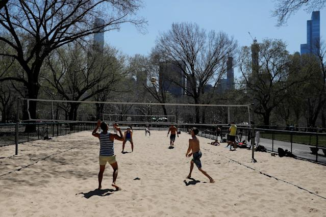Men enjoy the warm weather playing beach volleyball at Central Park in Manhattan, New York, U.S., April 23, 2018. REUTERS/Shannon Stapleton