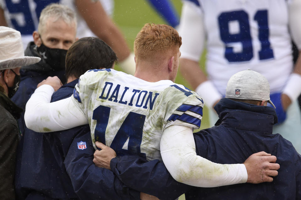 LANDOVER, MARYLAND - OCTOBER 25: Quarterback Andy Dalton #14 of the Dallas Cowboys is helped off the field after being hit and injured by Jon Bostic #53 (not pictured) of the Washington Football Team in the third quarter of the game at FedExField on October 25, 2020 in Landover, Maryland. (Photo by Patrick McDermott/Getty Images)