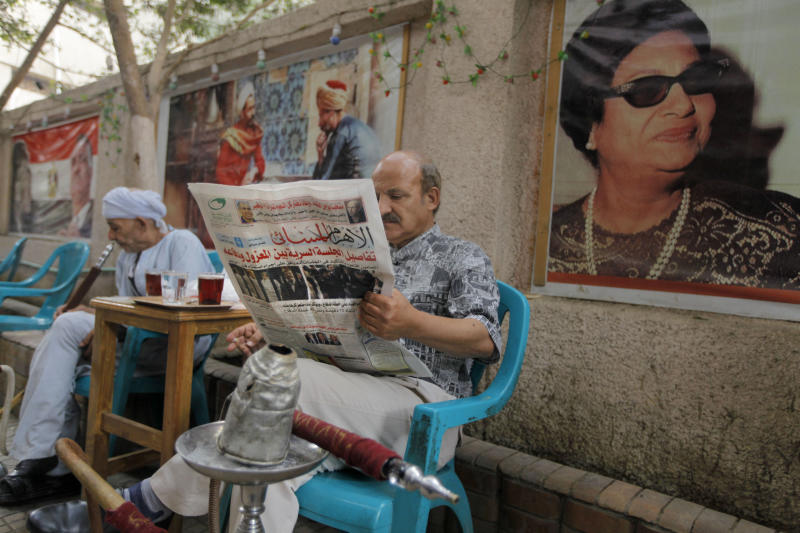 """An Egyptian man reads the daily Al-Ahram newspaper fronted by pictures of the trial of Egypt's ousted President Mohammed Morsi at a coffee shop in Cairo, Egypt, Tuesday, Nov. 5, 2013. After four months in secret detention, Egypt's deposed Islamist president defiantly rejected a court's authority to try him Monday, saying he was the country's """"legitimate"""" leader and those that overthrew him should face charges instead. The trial was then adjourned until Jan. 8 after several interruptions. Arabic headline reads, """"details of the ousted president closed trial."""" At right a painting showing Oum Kalthoum, one of the most famous Egyptian and Arab singers.(AP Photo/Amr Nabil)"""