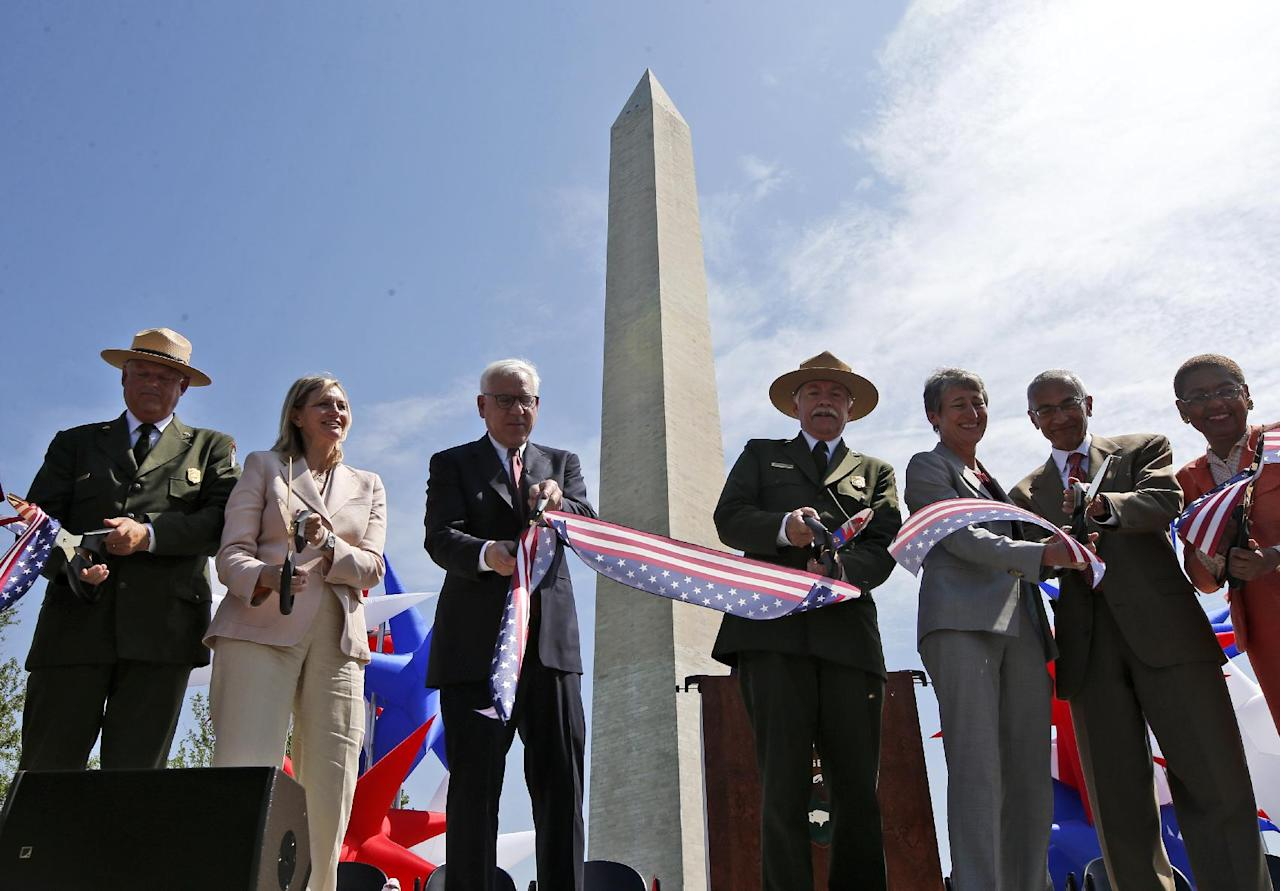 From left to right: Robert A. Vogel, Superintendent of the National Mall and Memorial Parks; Caroline L. Cunningham, President of the Trust for the National Mall; David M. Rubinstein, co-founder and co-chief executive officer of The Carlyle Group; Jonathan B. Jarvis, Director of the National Park Service; Interior Secretary Sally Jewell; White House Counsel John Podesta, and Del. Eleanor Holmes Norton, D-D.C., cut a ribbon at the Washington Monument in Washington, Monday, May 12, 2014, during a ceremony to celebrate its re-opening. The monument, which sustained damage from an earthquake in August 2011, reopened to the public today. (AP Photo)