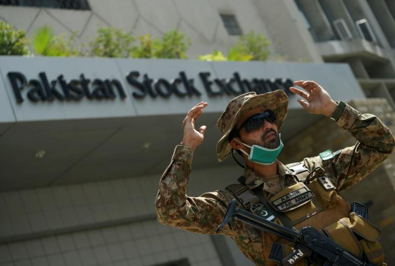 A paramilitary soldier gestures while standing guard outside the Pakistan Stock Exchange  after gunmen attacked the building