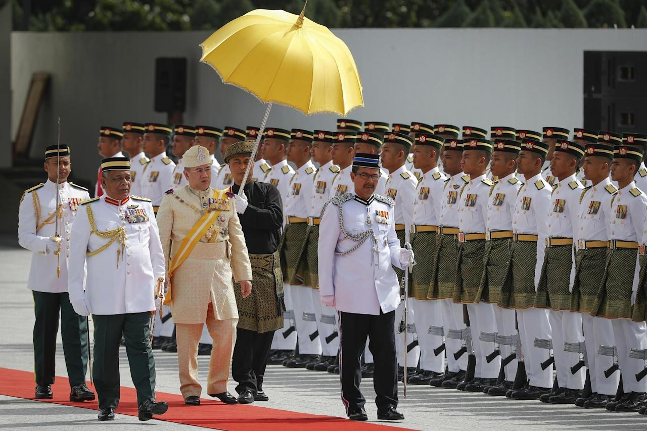 <p>Sultan Muhammad V, third from left, inspects a ceremonial guard of honor during his welcome ceremony in Kuala Lumpur, Malaysia, Tuesday, Dec. 13, 2016. Sultan Muhammad V of Kelantan will serve a five-year term as King of Malaysia from Tuesday. (AP Photo/Vincent Thian) </p>