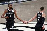 Brooklyn Nets forward Kevin Durant (7) slaps hands with Blake Griffin during the first half of Game 1 of the team's NBA basketball second-round playoff series against the Milwaukee Bucks on Saturday, June 5, 2021, in New York. The Nets won 115-107. (AP Photo/Adam Hunger)