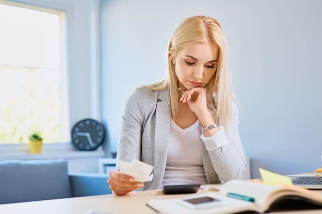 Sad young woman counting bills sitting at desk in home office
