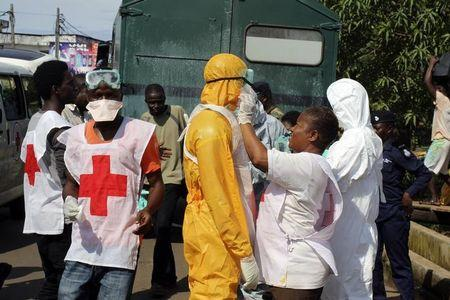 A health worker fixes another health worker's  protective suit in the Aberdeen district of Freetown