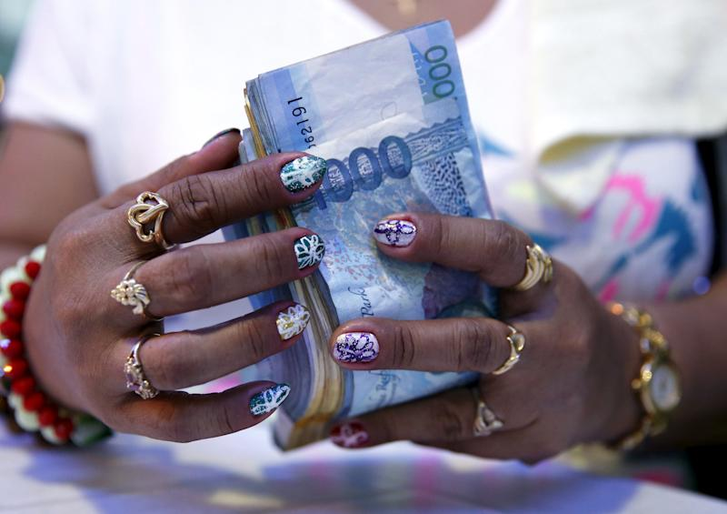 A casino financier wearing rings and with painted fingernails, counts money she collected from a gambler only moments before, in Angeles city, north of Manila, Philippines, May 25, 2015. (Photo: REUTERS/Erik De Castro)