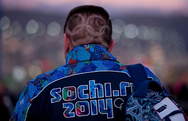 A Canadian fan with Olympic rings shaved into his hair makes his way to the opening ceremonies for the Sochi Winter Olympics Friday Feb. 7, 2014, in Sochi, Russia. (AP Photo/The Canadian Press, Adrian Wyld)