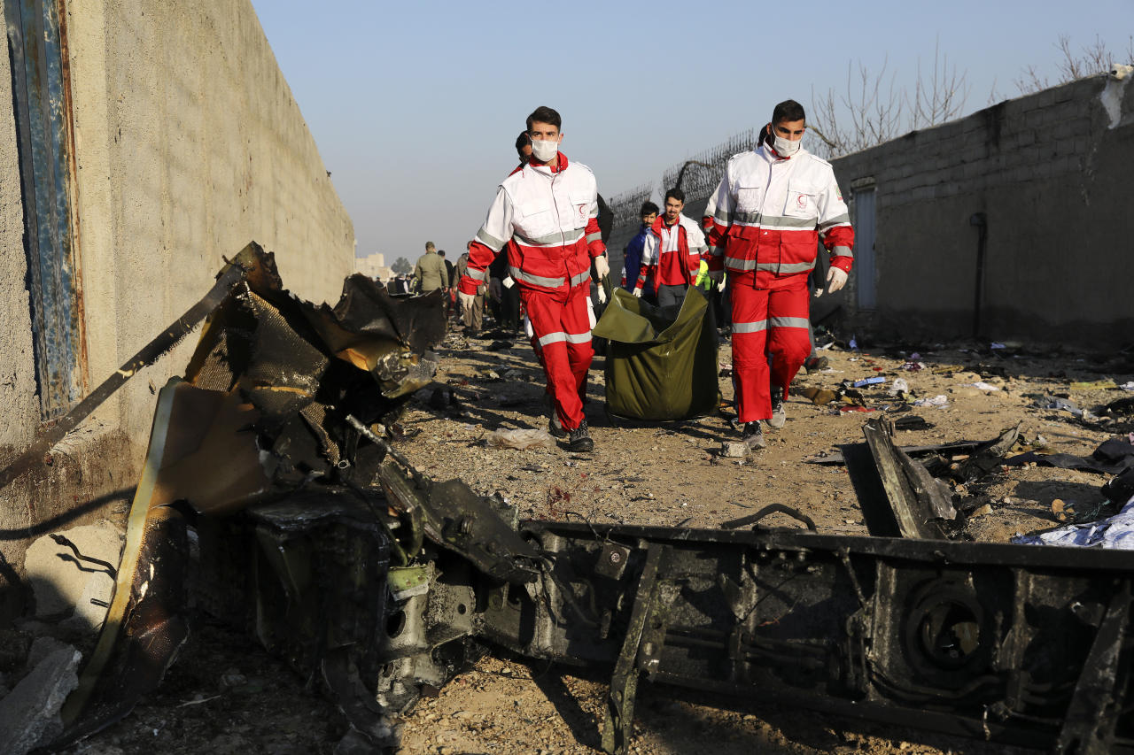 Rescue workers carry the body of a victim of an Ukrainian plane crash among debris of the plane in Shahedshahr, southwest of the capital Tehran, Iran, Wednesday, Jan. 8, 2020. A Ukrainian airplane carrying 176 people crashed on Wednesday shortly after takeoff from Tehran's main airport, killing all onboard. (AP Photo/Ebrahim Noroozi)
