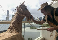 CORRECTS NAME - David Marriott poses with his paper horse Russel in his hotel room in Brisbane, Australia, April 3, 2021. While in quarantine inside his Brisbane hotel room, the art director was bored and started making a cowboy outfit from the paper bags his meals were being delivered in. His project expanded to include a horse and a clingfilm villain that he has daily adventures with, in images that have gained a huge online following. (David Marriott via AP)