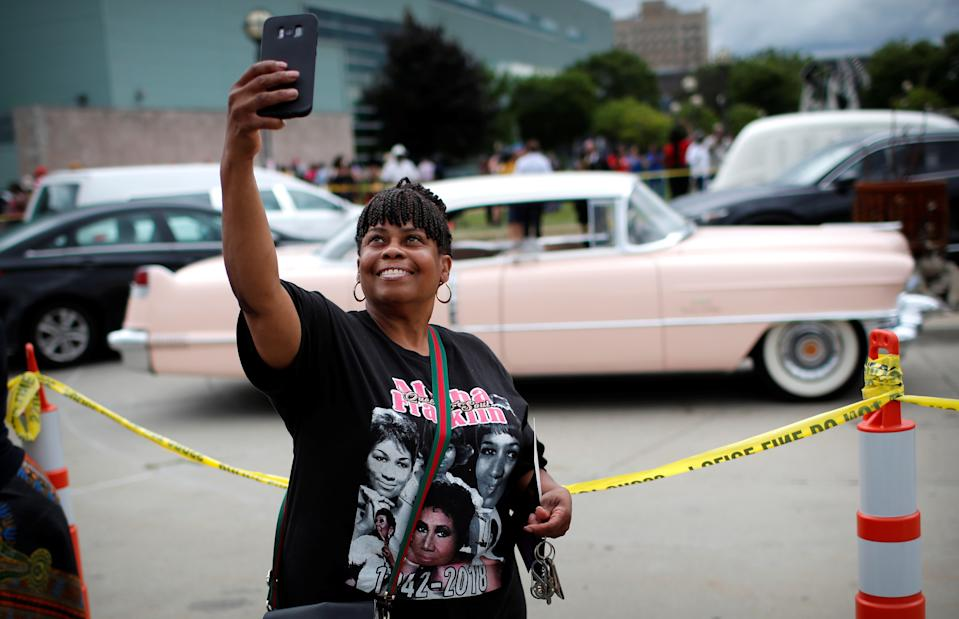 A woman takes a selfie photograph near a pink Cadillac outside the Charles H. Wright Museum of African American History on the second day of a public viewing of the late singer Aretha Franklin in Detroit, Michigan, U.S., August 29, 2018. REUTERS/Mike Segar