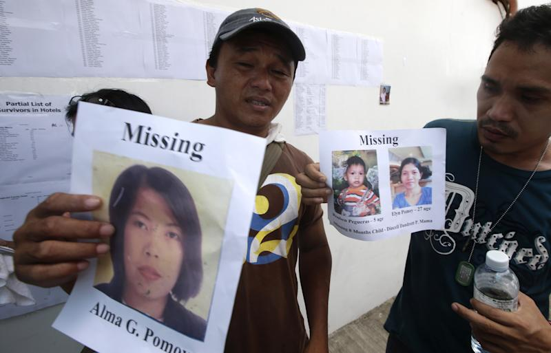 Ricky Pomoy, left, holds a print out of his missing wife Alma while Roderick Mama holds another print out of his missing wife and son outside the 2GO shipping company Sunday Aug. 18, 2013 in Cebu city, central Philippines. Divers plucked two more bodies from a sunken passenger ferry on Sunday and scrambled to plug an oil leak in the wreckage after a collision with a cargo ship. The accident near the central Philippine port of Cebu that has left 34 dead and more than 80 others missing. (AP Photo/Bullit Marquez)