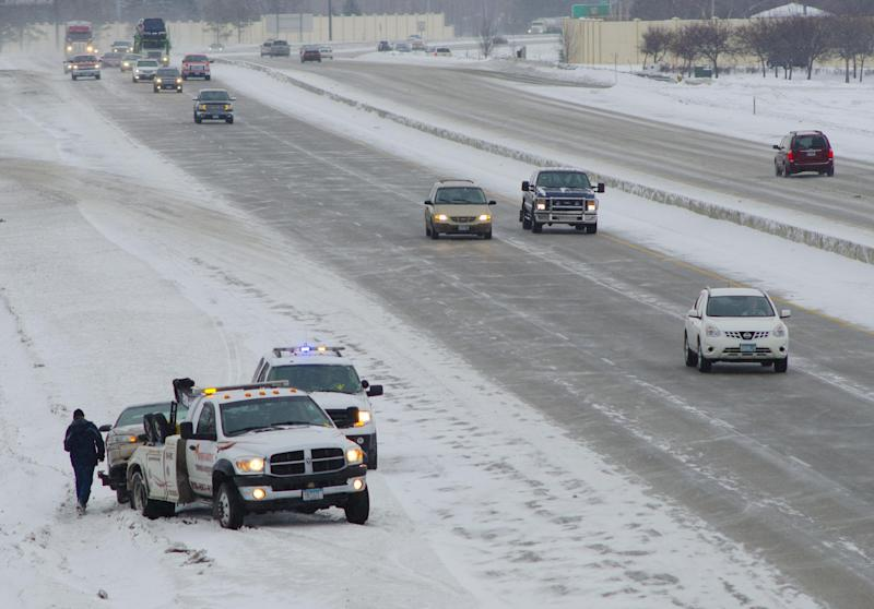 CORRECTS NAME OF PHOTOGRAPHER - A tow truck operator prepares to haul away a car involved in an accident on Interstate 94 in Fargo, N.D. on Monday, March 4, 2013. Overnight snow made travel treacherous across much of the upper Midwest. (AP Photo/Minnesota Public Radio,Nathaniel Minor)