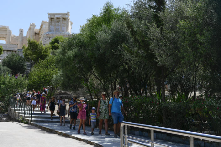 Tourists exit the ancient Acropolis, in Athens Greece, Tuesday, Aug. 3, 2021. Authorities in Greece have closed the Acropolis and other ancient sites during afternoon hours as a heatwave scorching the eastern Mediterranean continued to worsen. Temperatures reached 42 C (107.6 F) in parts of the Greek capital, as the extreme weather fueled deadly wildfires in Turkey and blazes across the region. (AP Photo/Michael Varaklas)