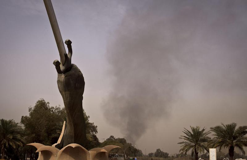 Black smoke from a car bomb attack is seen from the the Crossed Words monument in Baghdad, Iraq, Thursday, March, 14, 2013. A string of explosions tore through central Baghdad within minutes of each other on Thursday, followed by what appeared to be a coordinated assault by gunmen who battled security forces in the Iraqi capital, according to officials. Authorities say several people have been killed. (AP Photo/Maya Alleruzzo)