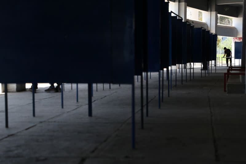 A worker places voting booths inside a polling station ahead of the upcoming referendum on a new Chilean constitution in Santiago