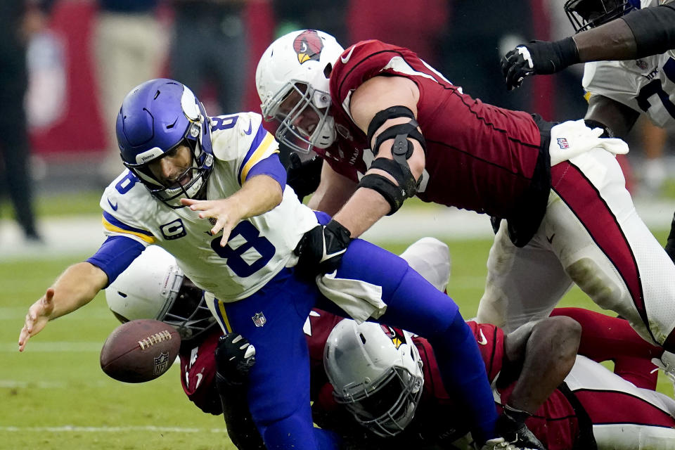 Minnesota Vikings quarterback Kirk Cousins (8) recovers his own fumble as Arizona Cardinals linebacker Markus Golden and defensive end J.J. Watt (99) make the hit during the second half of an NFL football game, Sunday, Sept. 19, 2021, in Glendale, Ariz. (AP Photo/Ross D. Franklin)