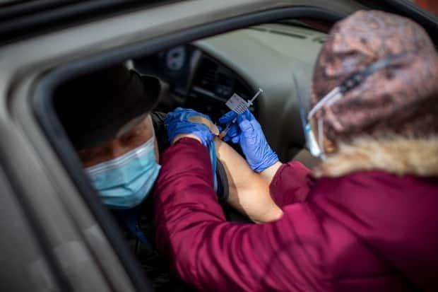 Health-care workers provide COVID-19 Pfizer vaccines at a drive-thru clinic in Central Park in Burnaby, B.C., on March 26.  (Ben Nelms/CBC - image credit)