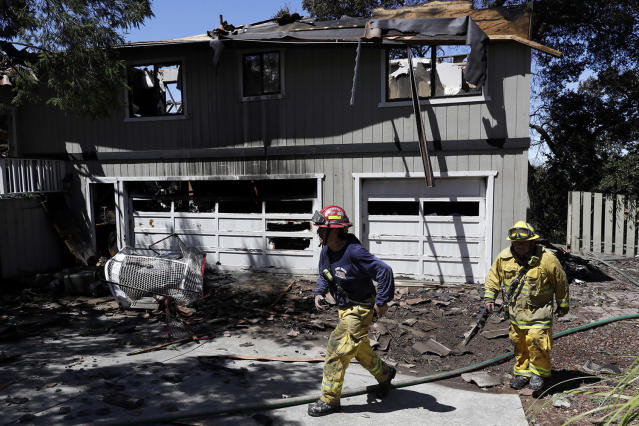<p>Firefighters Daniel Lizardo, right, and Victor Velasquez walk in front of a fire-ravaged home July 12, 2017, in San Jose, Calif. Relief was arriving after a rough stretch of wildfires all around the U.S. West, with firefighters slowly surrounding once-fierce blazes and evacuees starting to stream back home. (AP Photo/Marcio Jose Sanchez) </p>