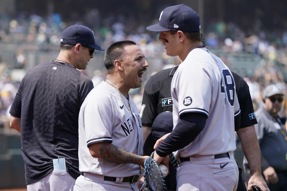New York Yankees pitcher Nestor Cortes Jr., center, reacts to umpires next to first baseman Anthony Rizzo, right, during the second inning of a baseball game against the Oakland Athletics in Oakland, Calif., Saturday, Aug. 28, 2021. (AP Photo/Jeff Chiu)