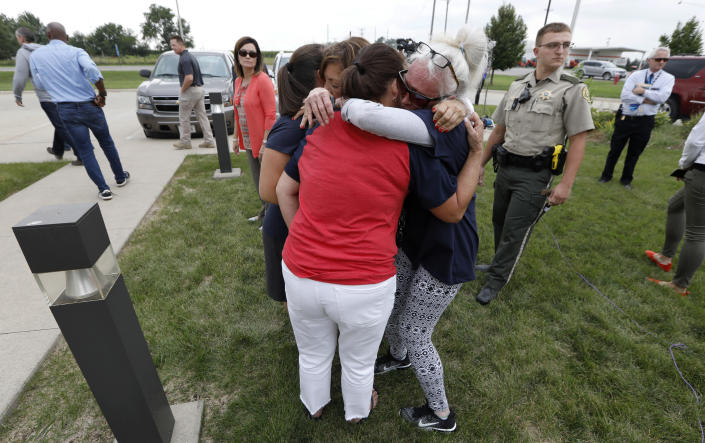 Friends and family of missing University of Iowa student Mollie Tibbetts react following a news conference, Tuesday, Aug. 21, 2018, in Montezuma, Iowa. Police say a man in the country illegally has been charged with murder in the death of Tibbetts who was reported missing from her hometown in the eastern Iowa city of Brooklyn in July 2018. (AP Photo/Charlie Neibergall)