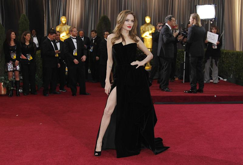 FILE - This Feb. 26, 2012 file photo shows Angelina Jolie posing before the 84th Academy Awards in the Hollywood section of Los Angeles. Every year fashion offers up the good, the bad and the ugly. But what the industry is really built on _ and consumers respond to _ is buzz. Jolie's leg, that peeked out of the high thigh-high slit of her Versace gown, was the most exciting appearance on the red carpet. (AP Photo/Amy Sancetta, file)