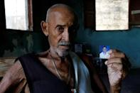 Juan Pulgar, 73, holds a picture of himself taken about a year ago, as he poses for a portrait in his house in Punto Fijo, Venezuela November 17, 2016. REUTERS/Carlos Garcia Rawlins