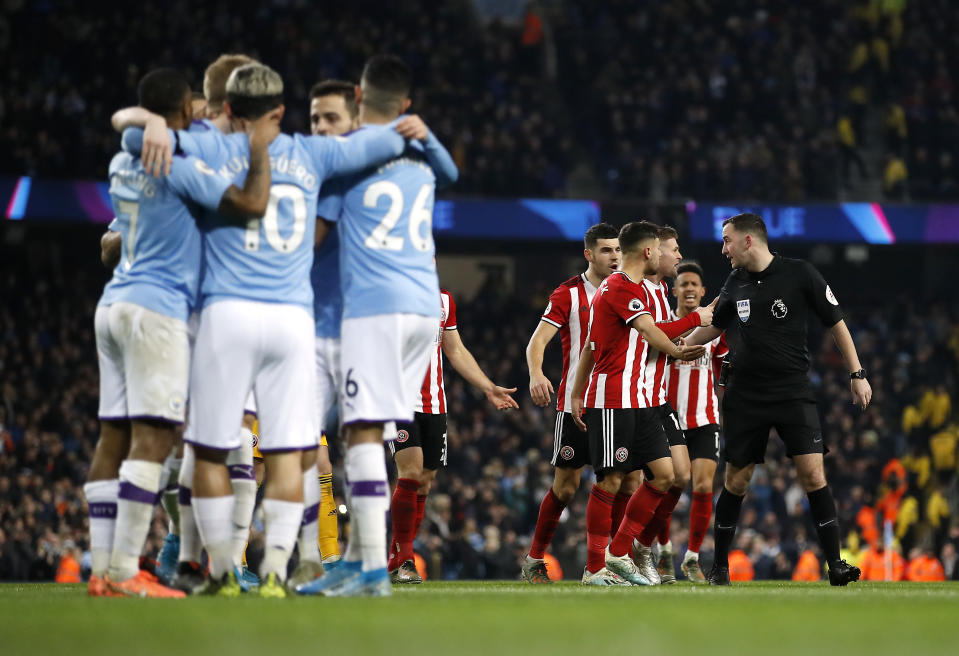Manchester City's Sergio Aguero (left) celebrates scoring his side's first goal of the game with team-mates as Sheffield United players argue with referee Chris Kavanagh (right) during the Premier League match at The Etihad Stadium, Manchester. (Photo by Martin Rickett/PA Images via Getty Images)