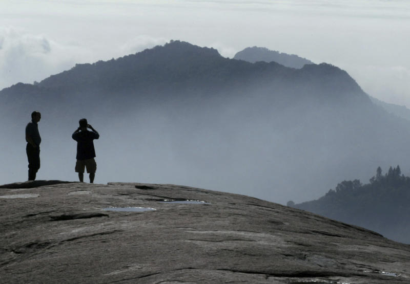 File-In this Oct. 3, 2016, file photo, Kyle Palmer, left, of Idaho waits as his son Lance Palmer of San Francisco, takes a photograph of the scene looking south from Beetle Rock at Giant Forest in Sequoia National Park, Calif. President Donald Trump will sign executive orders this week aimed at expanding offshore oil drilling and reviewing national monument designations made by his predecessors, continuing the Republican's assault on Democratic President Barack Obama's environmental legacy. (Eric Paul Zamora/The Fresno Bee vi AP, File)