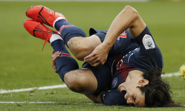 PSG's Edinson Cavani reacts as he falls during the French League One soccer match between Paris Saint-Germain and Bordeaux at the Parc des Princes stadium in Paris, Saturday, Feb. 9, 2019. (AP Photo/Christophe Ena)