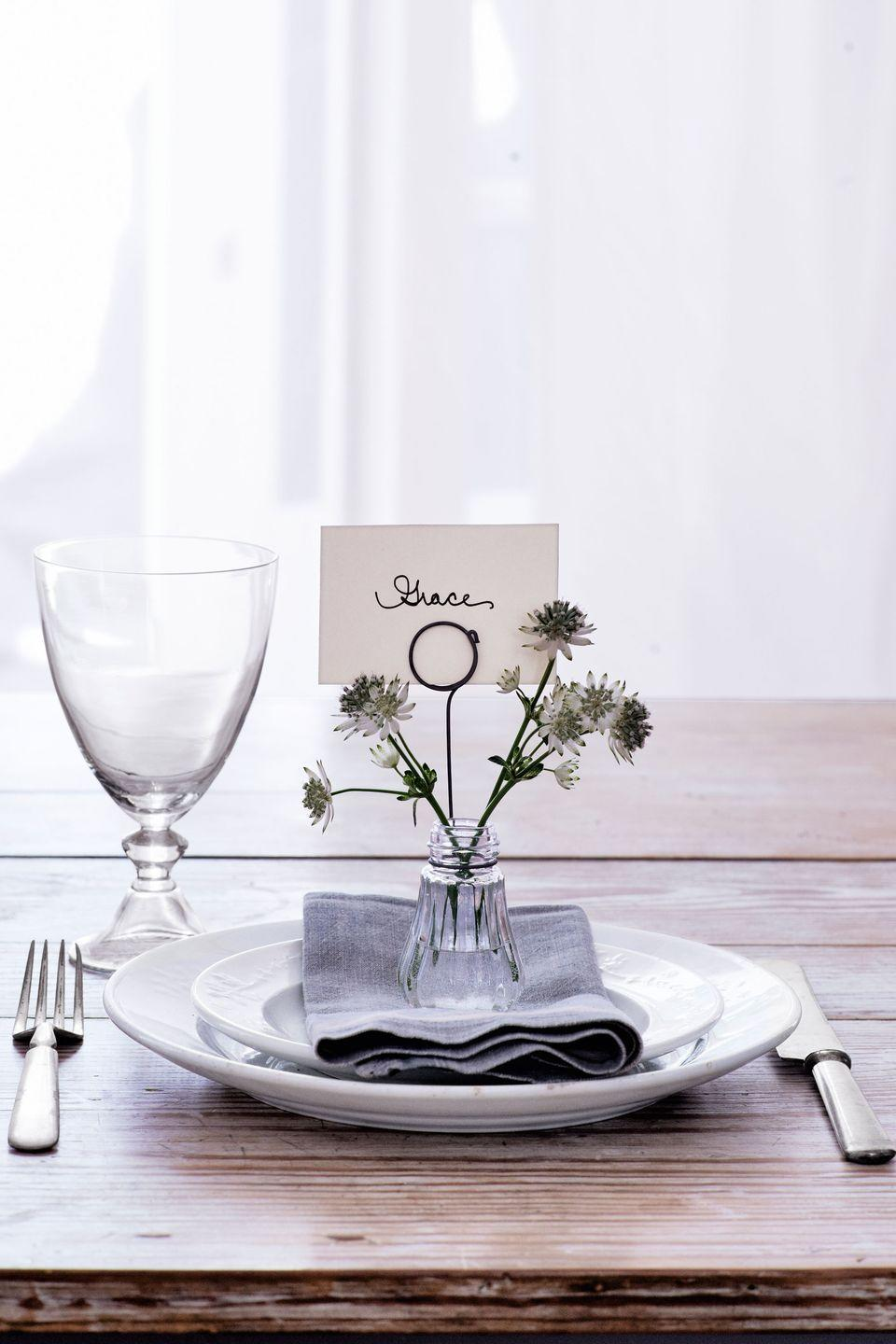 "<p>""Loop wire around a bottle to form a card holder, then pop in a mini-bouquet,"" says stylist <a href=""http://leanneford.com/"" rel=""nofollow noopener"" target=""_blank"" data-ylk=""slk:Leanne Ford"" class=""link rapid-noclick-resp"">Leanne Ford</a>.</p><p><a class=""link rapid-noclick-resp"" href=""https://www.amazon.com/Bottles-Camping-Project-Jewelry-Stranded/dp/B010RGS6DE/?tag=syn-yahoo-20&ascsubtag=%5Bartid%7C10050.g.1538%5Bsrc%7Cyahoo-us"" rel=""nofollow noopener"" target=""_blank"" data-ylk=""slk:SHOP GLASS BOTTLES"">SHOP GLASS BOTTLES</a></p>"