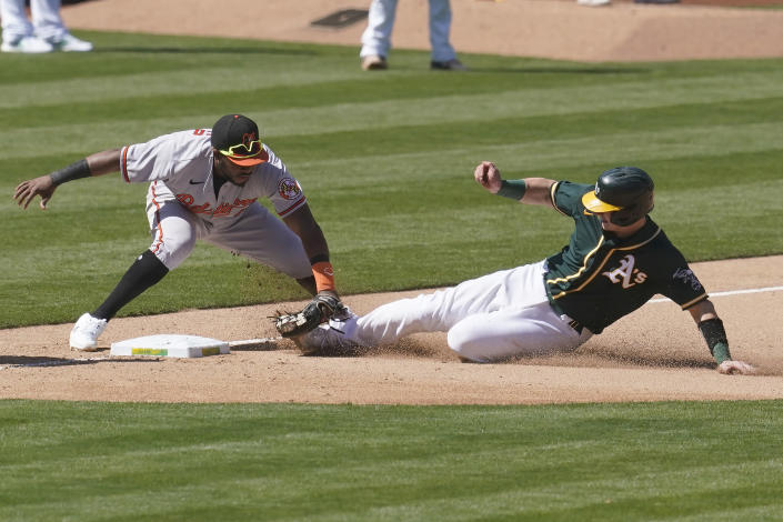 Oakland Athletics' Sean Murphy, right, is tagged out trying to advance to third base by Baltimore Orioles third baseman Maikel Franco, left, during the seventh inning of a baseball game in Oakland, Calif., Sunday, May 2, 2021. (AP Photo/Jeff Chiu)