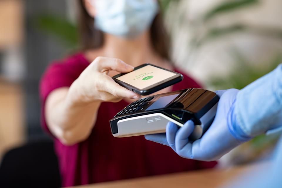 Close up hand of customer paying with smartphone. Cashier hand holding credit card reader machine and wearing protective disposable gloves at bar counter, while client holding phone for NFC payment. Woman wearing face mask while paying bill with mobile phone during Covid-19 pandemic.