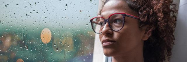 Sad african american girl looking out of the window on rainy weather
