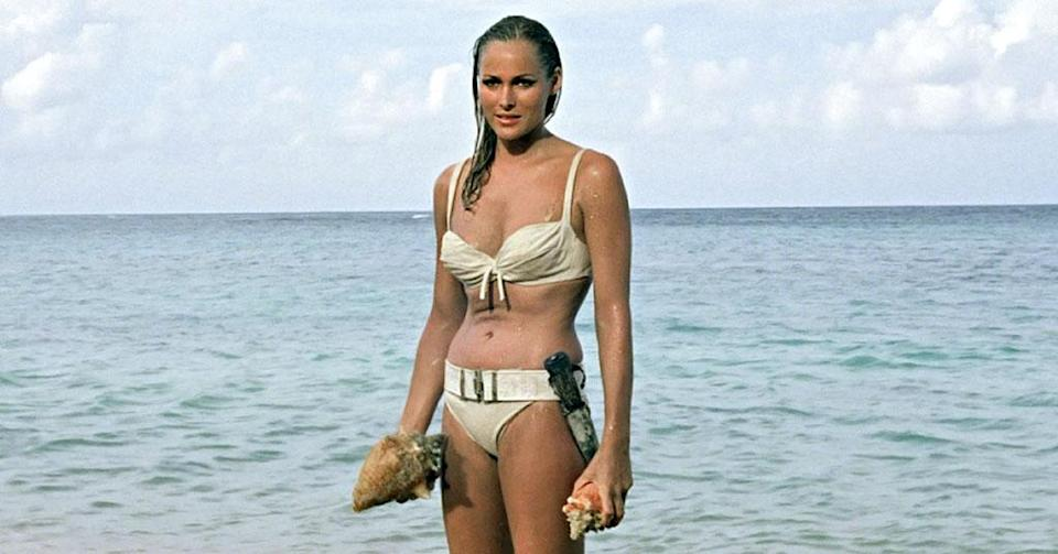 """<p>You might notice more than one moment from <em>Dr. No</em> on this list. It's not because it's such a great film. But it was the first and, as such, features several essential touchstone scenes that would continue to pop up in each subsequent chapter. Take the first appearance of the <a href=""""https://ew.com/movies/bond-girl-fashion/"""" rel=""""nofollow noopener"""" target=""""_blank"""" data-ylk=""""slk:&quot;Bond Girl.&quot;"""" class=""""link rapid-noclick-resp"""">""""Bond Girl.""""</a> Yes, that phrase is as outdated and retrograde now as the whole notion of a gorgeous damsel who requires saving. Still, <a href=""""https://ew.com/tag/ursula-andress/"""" rel=""""nofollow noopener"""" target=""""_blank"""" data-ylk=""""slk:Ursula Andress"""" class=""""link rapid-noclick-resp"""">Ursula Andress</a>' bikini-clad emergence from the surf (with a dagger strapped around her waist) as Honey Ryder belongs near the top of any list of indelible Bond moments. Throughout the series, it was often imitated but never equaled.</p>"""