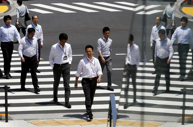 FILE PHOTO: Office workers are reflected in a glass railing as they cross street during lunch hour in Tokyo